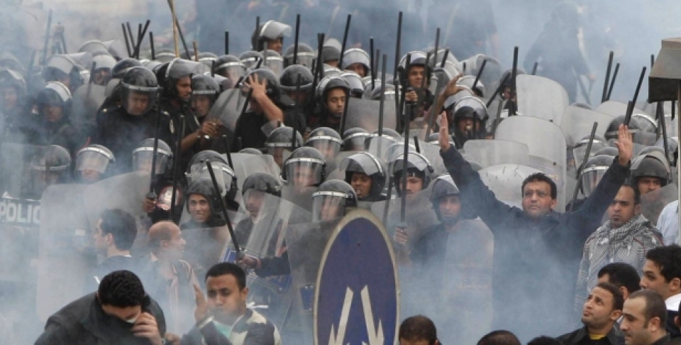 In this Jan. 28, 2011 photo, Egyptian anti-government activists clash with riot police in Cairo, Egypt. (AP Photo/Ben Curtis, File)
