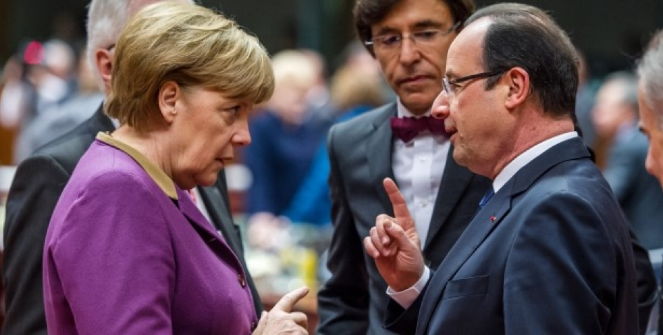 German Chancellor Angela Merkel speaks with French President Francois Hollande during a round table meeting at an EU summit in Brussels. (AP Photo/Geert Vanden Wijngaert)