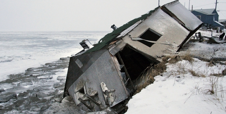 In this Dec. 2006 photo, an abandoned house at the west end of Shishmaref, Alaska, sits on the beach after sliding off during a fall storm in 2005. (AP Photo/Diana Haecker, File)
