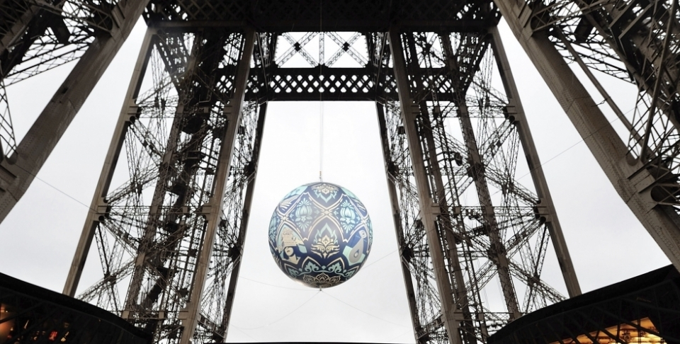 American street artist Shepard Fairey, aka Obey's piece 'Earth Crisis', a giant sphere themed on environment hangs between the first and second floor of the Eiffel Tower in Paris on Nov. 20, 2015. The piece was on display leading up to the 2015 climate change conference. (AP Photo/Binta Epelly)