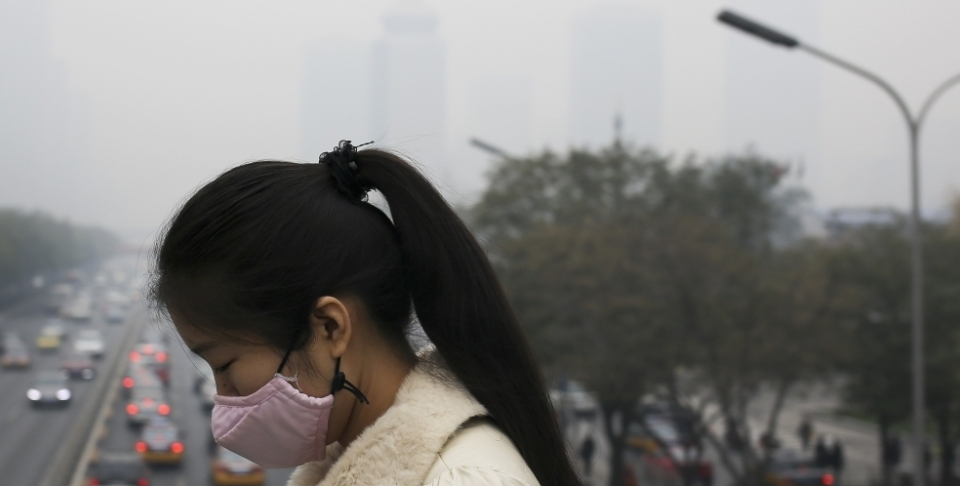 A woman wears a mask to protect herself from pollutants on a hazy day in Beijing. At the G20, the U.S. and China jointly confirmed the ratification of the Paris Agreement.  (AP Photo/Andy Wong)