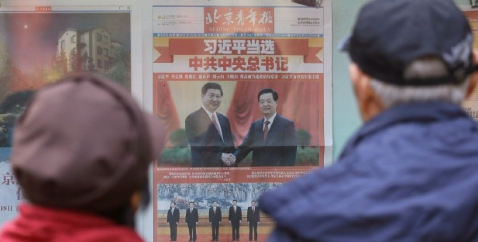 A Chinese couple look at a newspaper carrying photos of new General Secretary of the Communist Party of China Xi Jinping, top left, shaking hands with his predecessor Hu Jintao, top right, and Xi and other members of the party leadership in Beijing, China (AP Photo/Lee Jin-man).