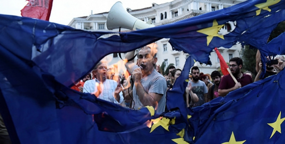 Members of left wing parties burn a European Union flag during a protest in the northern Greek port city of Thessaloniki. (AP Photo/Giannis Papanikos)