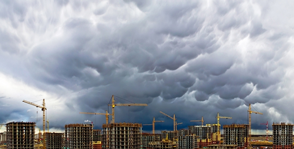 Construction cranes appear along a stormy skyline. (Shutterstock)