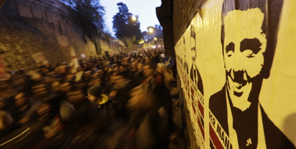 Protesters pass a poster of Italian Premier Matteo Renzi in Rome (AP Photo/Andrew Medichini)