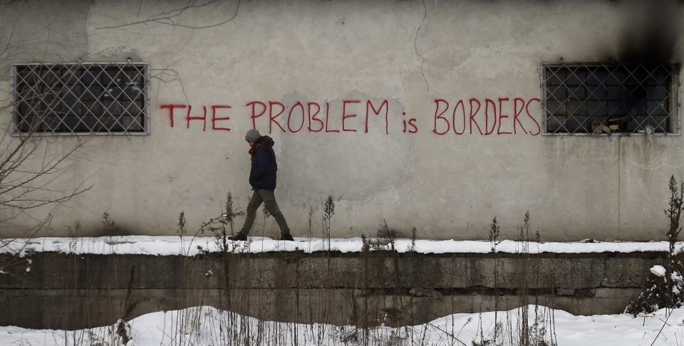 A migrant passes graffiti on a warehouse in Belgrade serving as a make-shift shelter for hundreds of men trying to reach Western Europe (AP Photo/Darko Vojinovic)