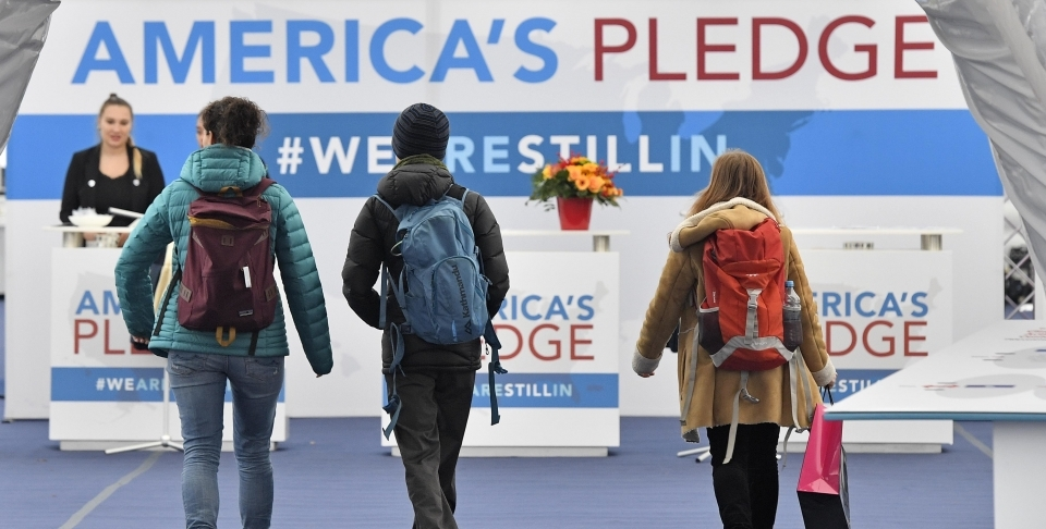 Visitors enter the US Climate Action Center at the COP 23 Fiji UN Climate Change Conference in Bonn, Germany, Thursday, Nov. 9, 2017. (AP Photo/Martin Meissner)