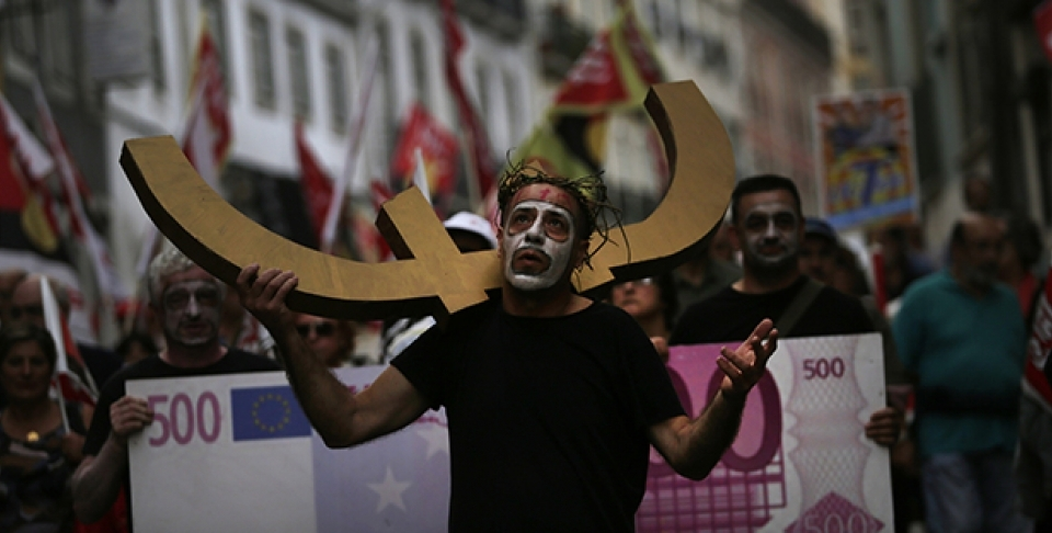 A man carries a euro currency symbol on his shoulder as he marches with others towards the parliament during a protest against austerity measures in Portugal. (AP Photo/Francisco Seco)