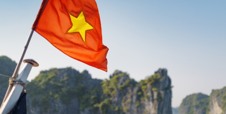 The flag of Vietnam (red flag with a gold star) fluttering on ship in the Halong Bay at the Gulf of Tonkin of the South China Sea, Vietnam. Karst towers-isles are visible in background/Shutterstock