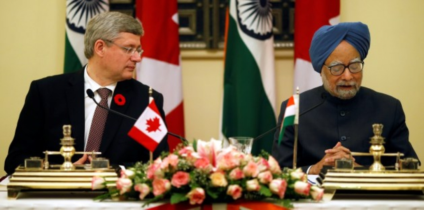 Indian Prime Minister Manmohan Singh, right, reads out a speech as his Canadian counterpart Stephen Harper looks towards him  during signing of agreements between the two countries in New Delhi, India, Tuesday, Nov. 6, 2012. (AP Photo/Saurabh Das)