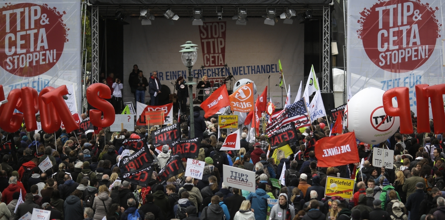 Protesters gather in front of the main stage during a demonstration of thousands of people against the planned Transatlantic Trade and Investment Partnership, TTIP, and the Comprehensive Economic and Trade Agreement, CETA, ahead of the visit of US President Barack Obama in Hannover, Germany, Saturday, April 23, 2016. (AP Photo/Markus Schreiber)