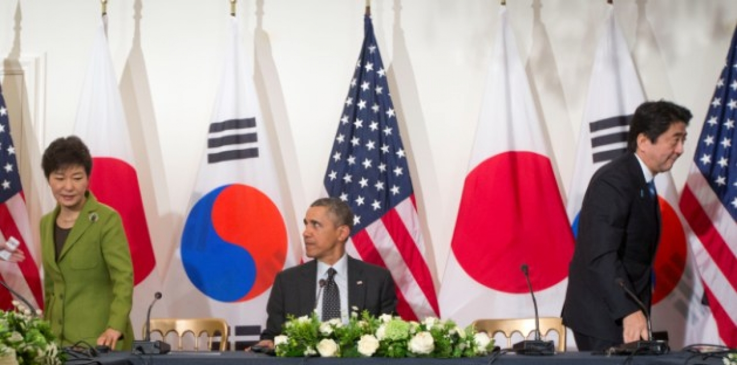 President Barack Obama watches as South Korean President Park Geun-hye, left, and Japanese Prime Minister Shinzo Abe, leave their seats, March 25, 2014, during the start of their trilateral meeting at the US Ambassador's Residence in the Hague, Netherlands. (AP Photo/Pablo Martinez Monsivais)
