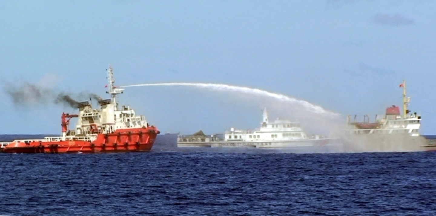 A Chinese ship shoots water cannon at a Vietnamese vessel, while a Chinese Coast Guard ship, center, sails alongside in the South China Sea, off Vietnam's coast, May 7, 2014. Chinese ships are ramming and spraying water cannons at Vietnamese vessels trying to stop Beijing from setting up an oil rig in the South China Sea, according to Vietnamese officials (AP Photo/Vietnam Coast Guard).