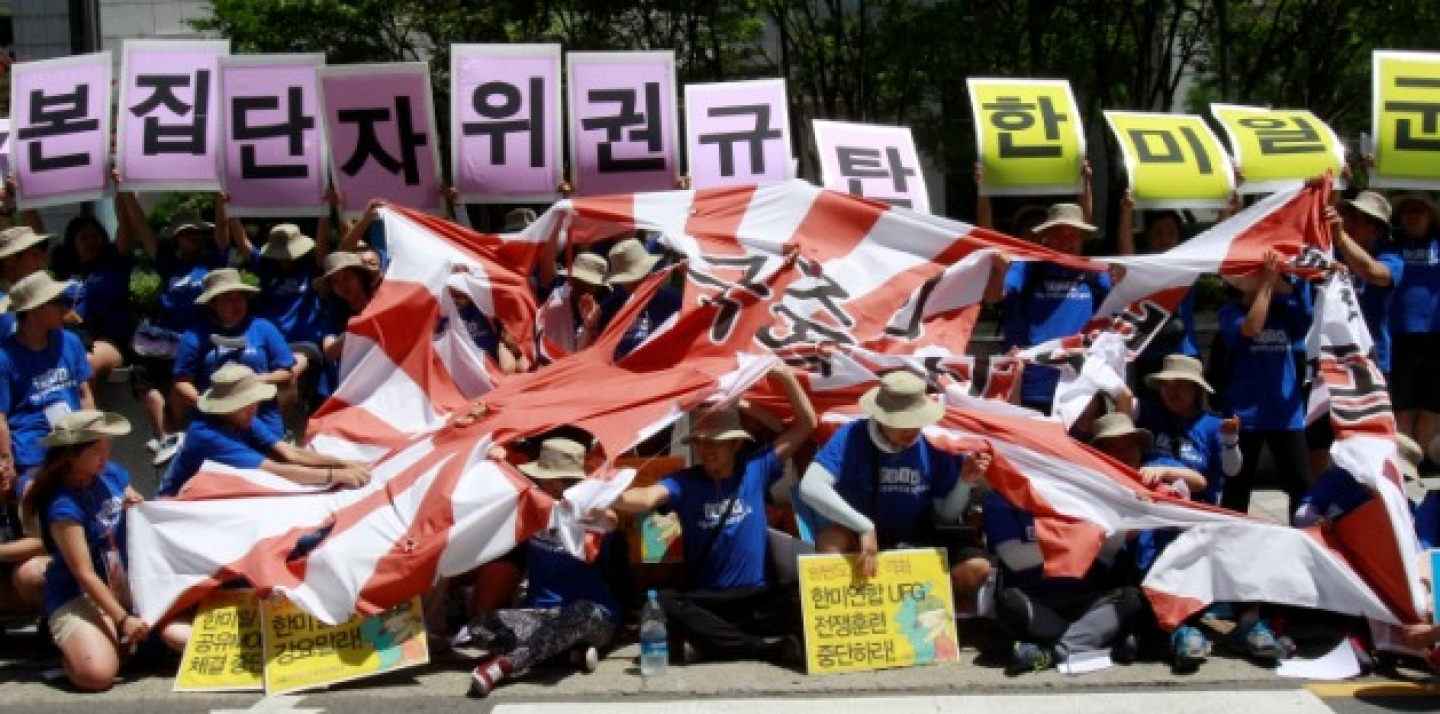 "Protesters tear a Japanese rising sun flag during a rally against the Japanese government, demanding not to move toward exercising the right to collective self-defense seen as a prelude to the revival of Japan's past militarism, near the Japanese Embassy in Seoul, South Korea, Friday, Aug. 8, 2014. The cards read ""Oppose collective self-defense plan."" (AP Photo/Ahn Young-joon)"