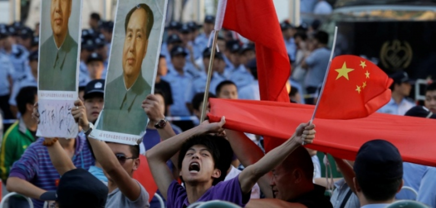 A Chinese man shouts anti-Japan slogans with Chinese national flags near portraits of the late Communist leader Mao Zedong in front of the Japanese Embassy in Beijing, September 2012. (AP Photo/Ng Han Guan)
