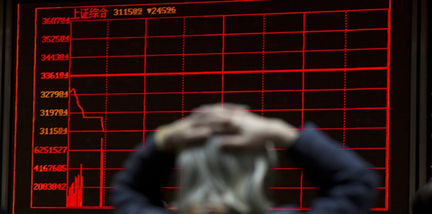 A woman reacts near a display board showing the plunge in the Shanghai Composite Index at a brokerage in Beijing, China, on January 7, 2016. (AP Photo/Ng Han Guan, File)