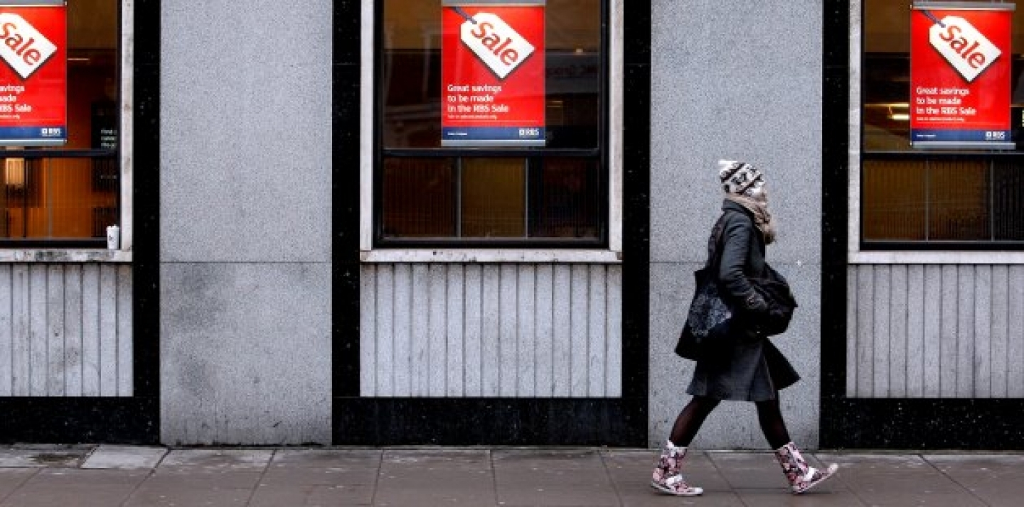 A woman passes a bank advertising a sale on its products, behind Oxford Street in London. (AP Photo/Kirsty Wigglesworth)