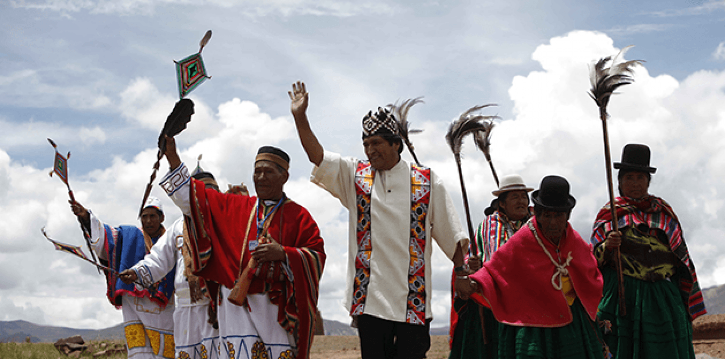 Bolivia's President Evo Morales, center, waves as he is escorted by shamans during an indigenous religious ceremony that recognizes Morales as the country's leader in Tiwanaku, Bolivia. (AP Photo/Dado Galdieri)