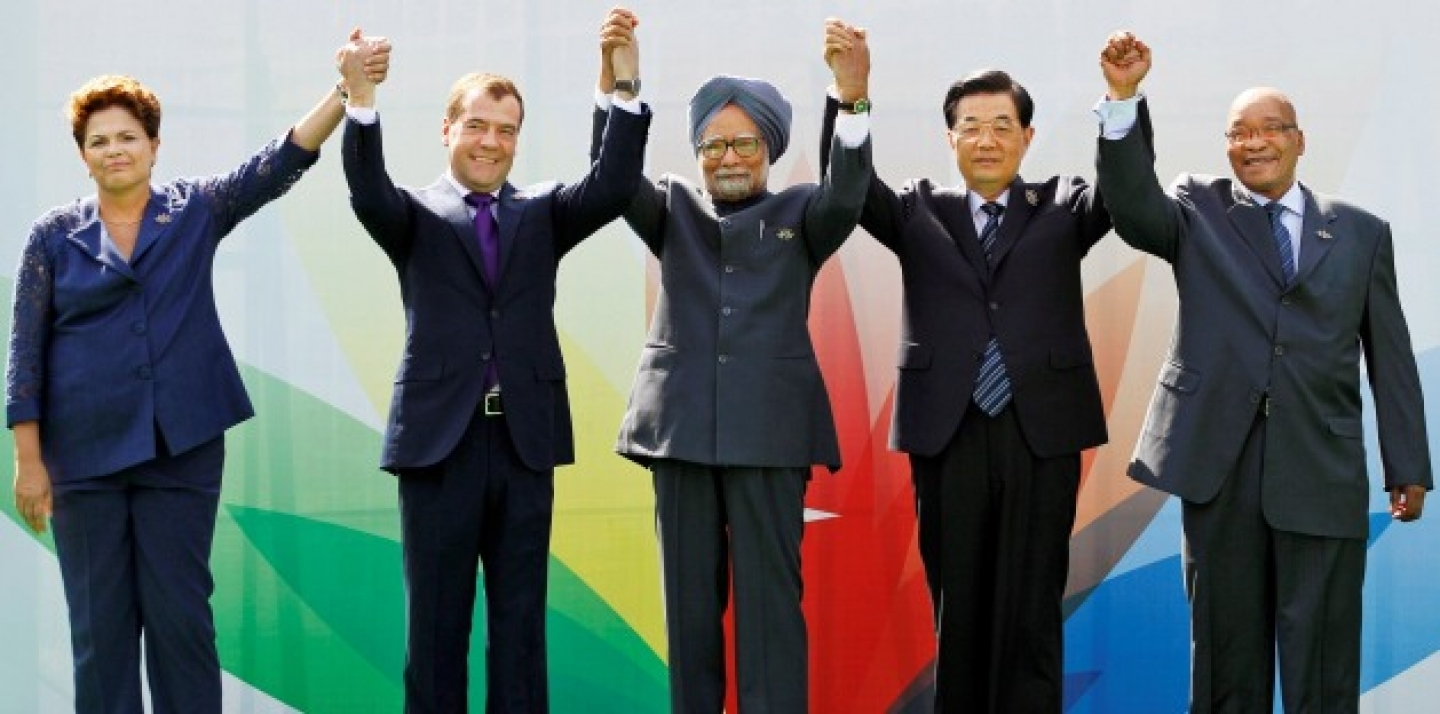 Leaders raise their arms together during the group picture for the BRICS 2012 Summit in New Delhi, India (AP Photo/Saurabh Das).