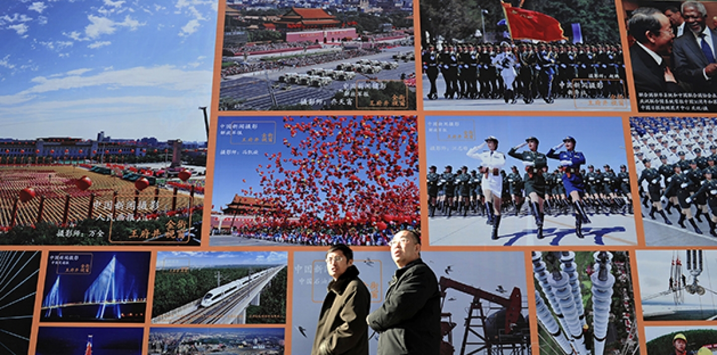 Two Chinese men walk past a huge billboard featuring photos of China's development in previous years in Beijing. (AP Photo/Andy Wong)