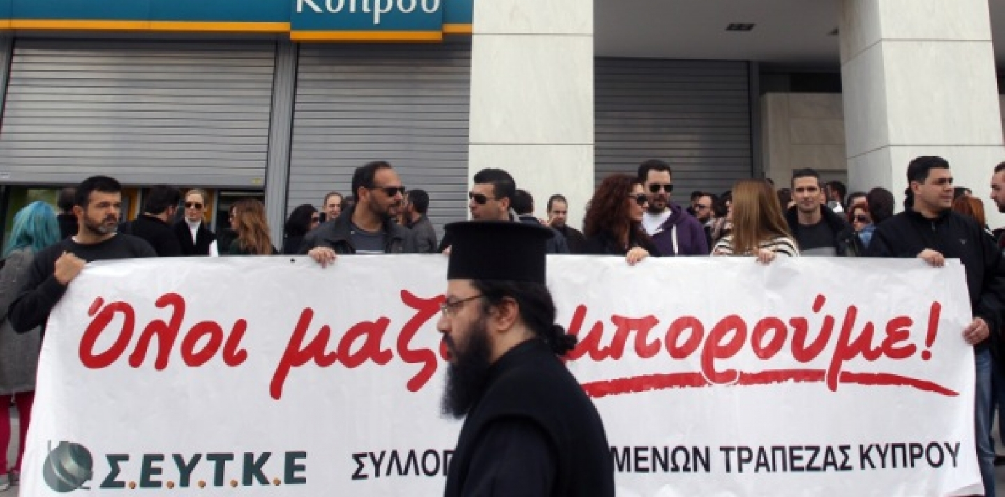 A Greek Orthodox priest passes employees of the Bank of Cyprus holding a banner that reads: ''All Together...We Can'' during a rally outside headquarters in Athens on Wednesday, March 20, 2013, following Cypriot lawmakers' rejection of a bailout plan. (AP Photo/Thanassis Stavrakis)