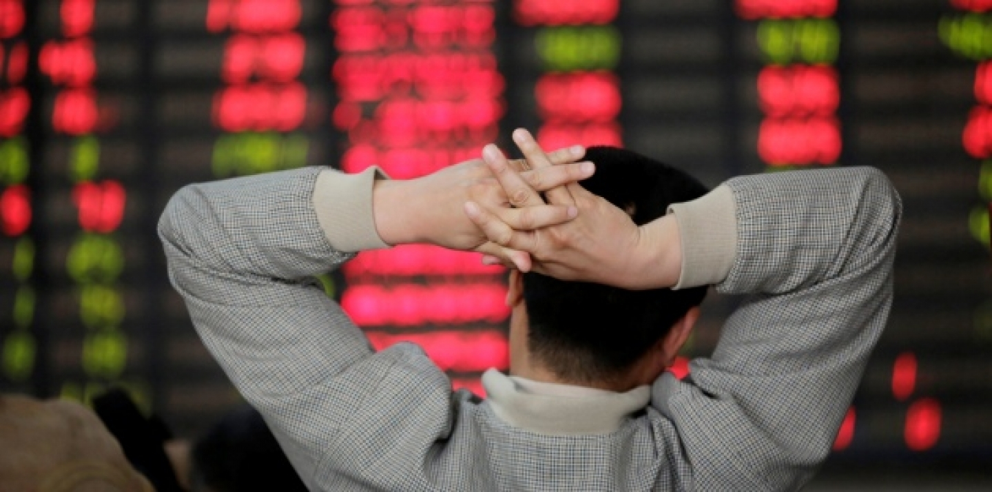 An investor looks at the stock price monitor at a private securities company in Shanghai, China Monday, April 8, 2013. (AP Photo/Eugene Hoshiko)
