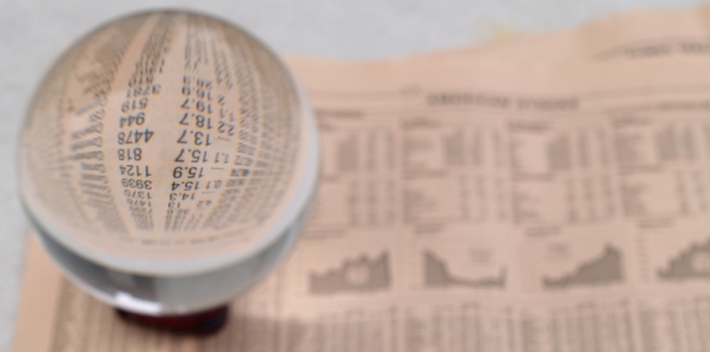 A crystal ball sits on the financial section of a newspaper (Shutterstock).