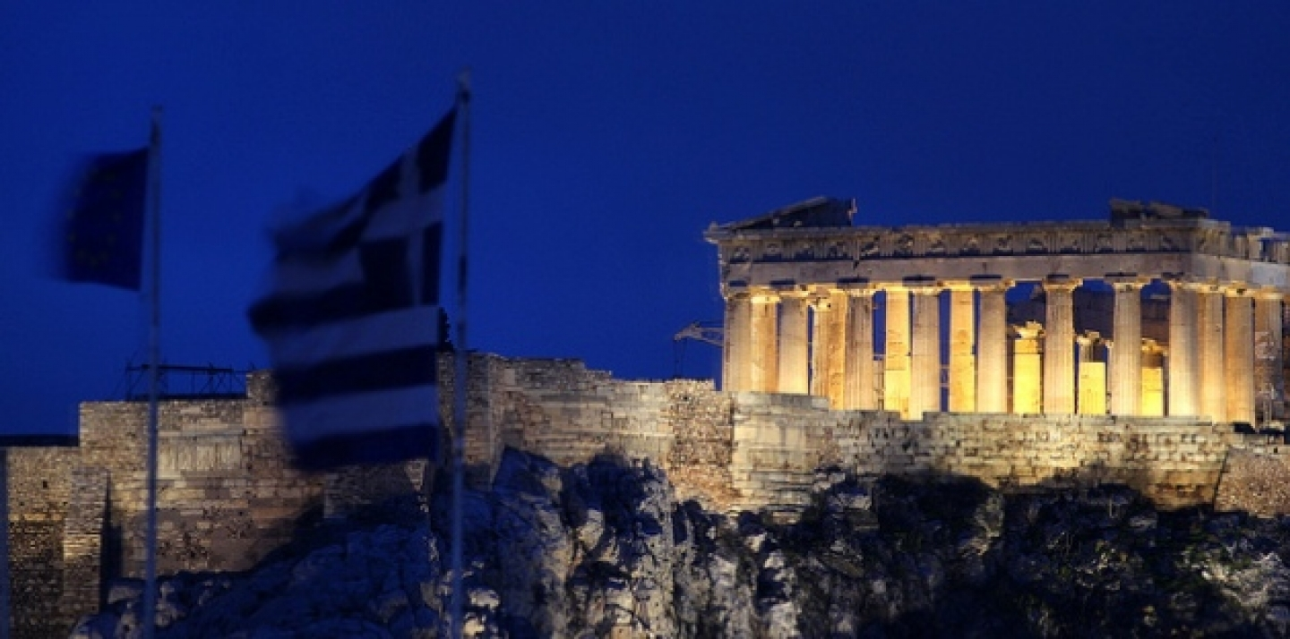 The flags of Greece and European Union flutter from the roof of the Finance Minister with the ancient Parthenon temple in Athens behind (AP Photo/Dimitris Messinis).