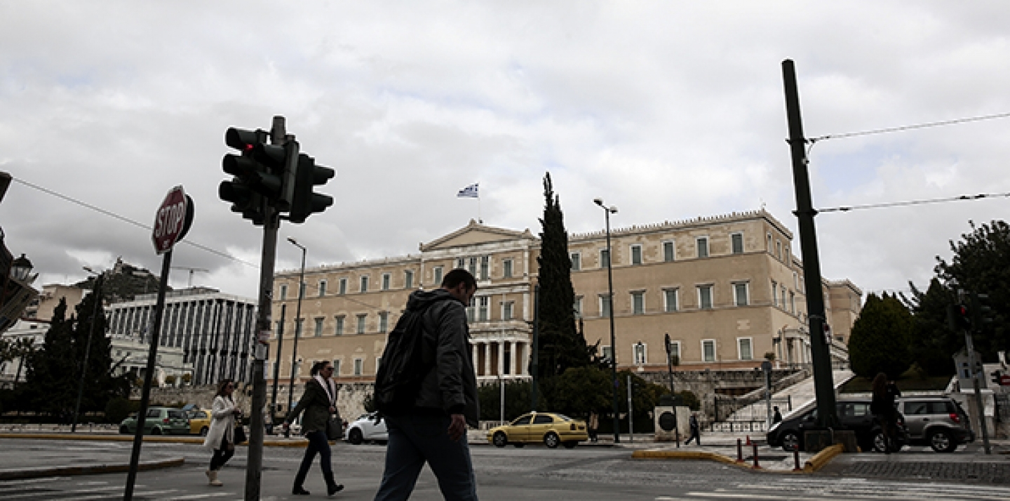 People make their way in front of the parliament in Athens, Monday, Feb. 23, 2015. Greece will present a list of proposed reforms to debt inspectors on Monday to get final approval for an extension to its rescue loans. (AP Photo/Yorgos Karahalis)