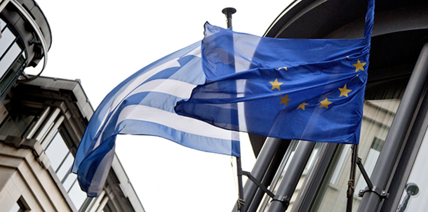 The Greek, left, and EU flag flap in the wind outside the Greek embassy in Brussels. (AP Photo/Virginia Mayo)