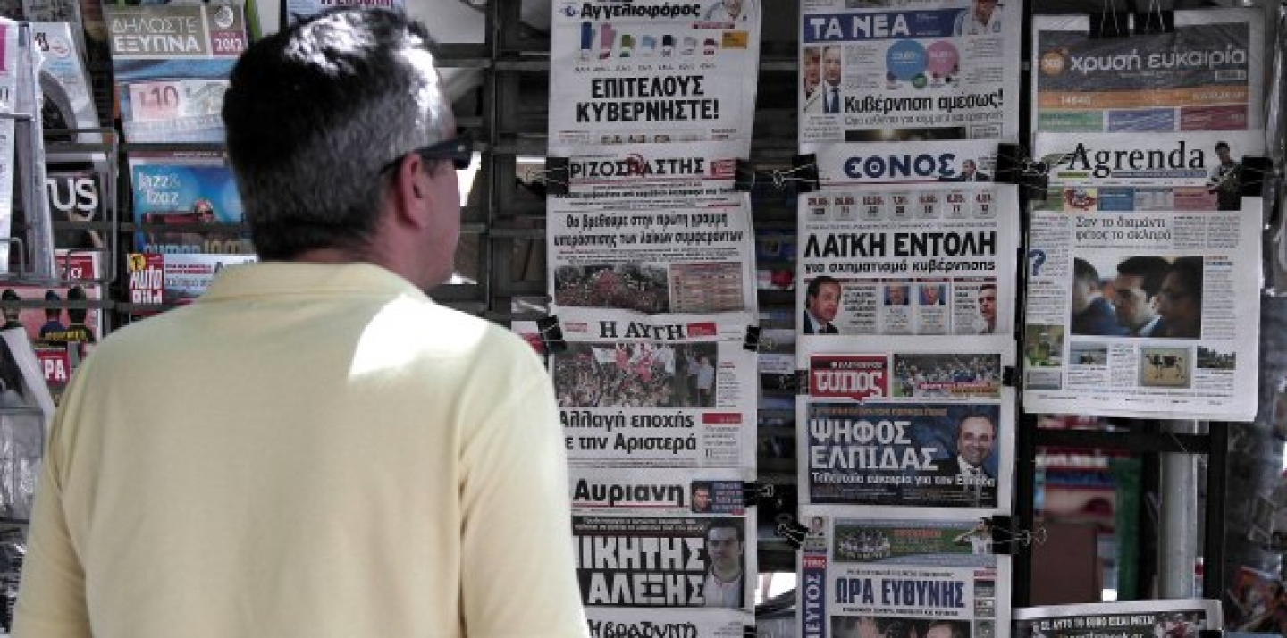 A man reads newspaper headlines displayed at a kiosk following the election of the pro-bailout New Democracy party in the Greek national election. (AP Photo/Dimitri Messinis)