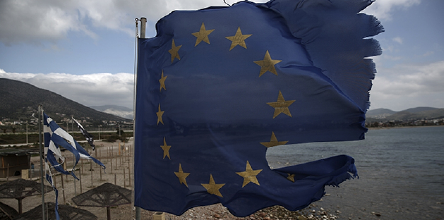 Ruined EU and Greek flags fly in tatters from a flag pole at a beach at Anavissos village, southwest of Athens, on Monday, March 16, 2015. (AP Photo/Yorgos Karahalis)