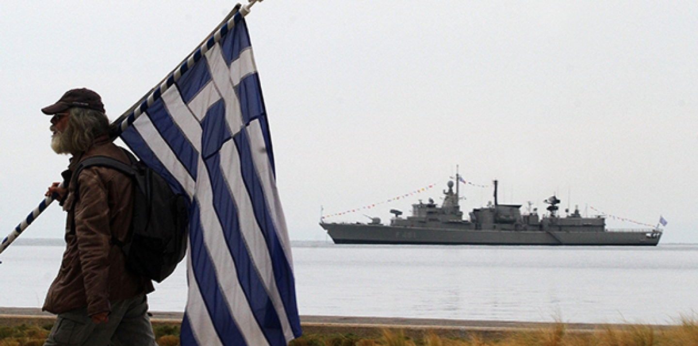 A spectator holds a Greek flag as a Greek Navy vessel is moored at Thermaikos Gulf during the annual military parade in the northern Greek port city of Thessaloniki.  (AP Photo/Grigoris Siamidis)
