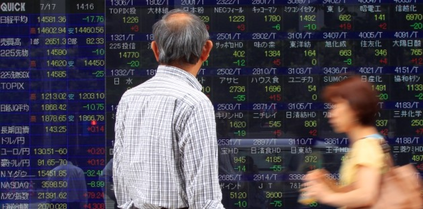 A man watches an electronic stock indexes in Tokyo, Japan, Wednesday, July 17, 2013. Asian stock markets were mixed Wednesday as investors remained cautious ahead of testimony from U.S. Federal Reserve Chairman Ben Bernanke. (AP Photo/Shizuo Kambayashi)