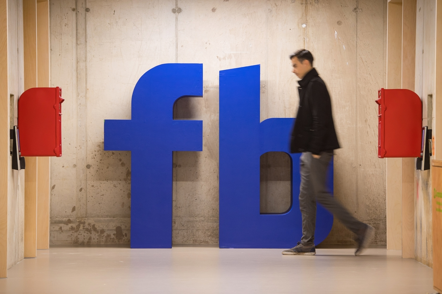 A man walks past a Facebook logo at Facebook's headquarters at Rathbone Place in London. (Reuters/Dominic Lipinski)