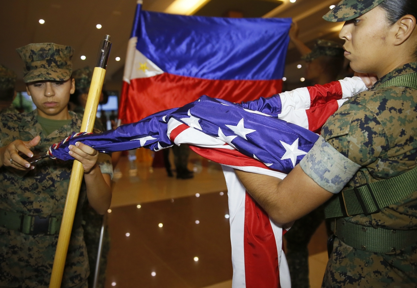 A U.S. Marine and her Philippine counterpart fold their flags near Manila on Oct. 11. Marines ended joint combat drills a day early after President Rodrigo Duterte criticized the U.S. (AP Photo/Bullit Marquez)