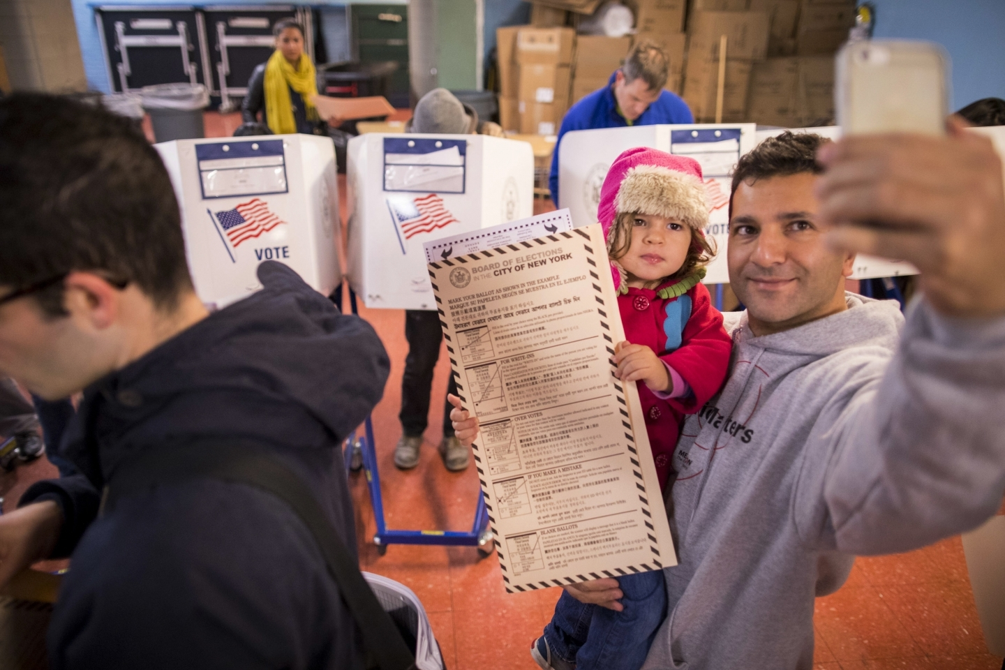 A man takes a selfie with his child as he waits to vote at a polling station in Brooklyn borough of New York on Tuesday, Nov. 8, 2016. (AP Photo/Alexander F. Yuan)