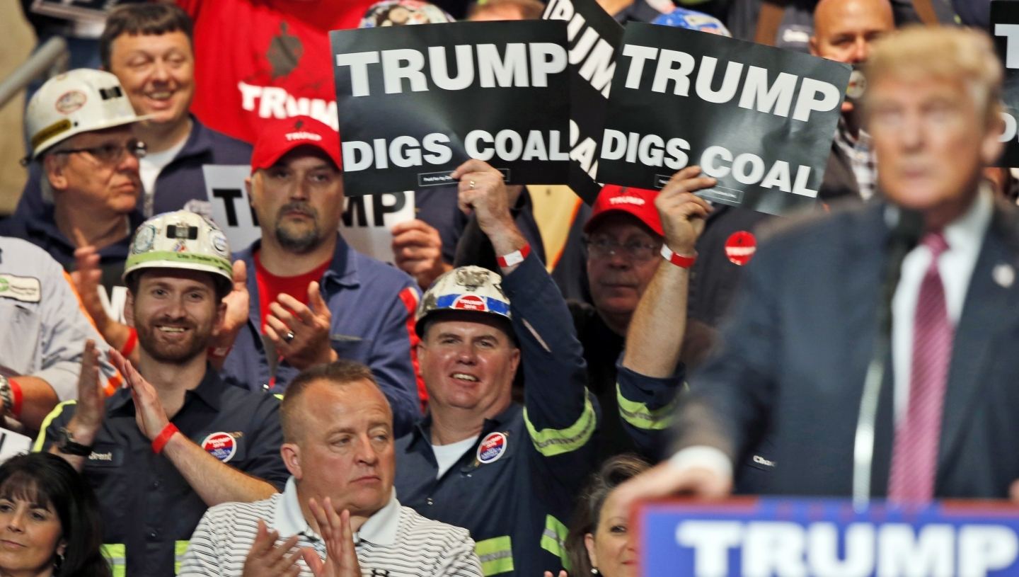 Coal miners wave signs as Republican presidential candidate Donald Trump speaks during a rally in Charleston, W.Va. in May 2016. (AP Photo/Steve Helber, File)
