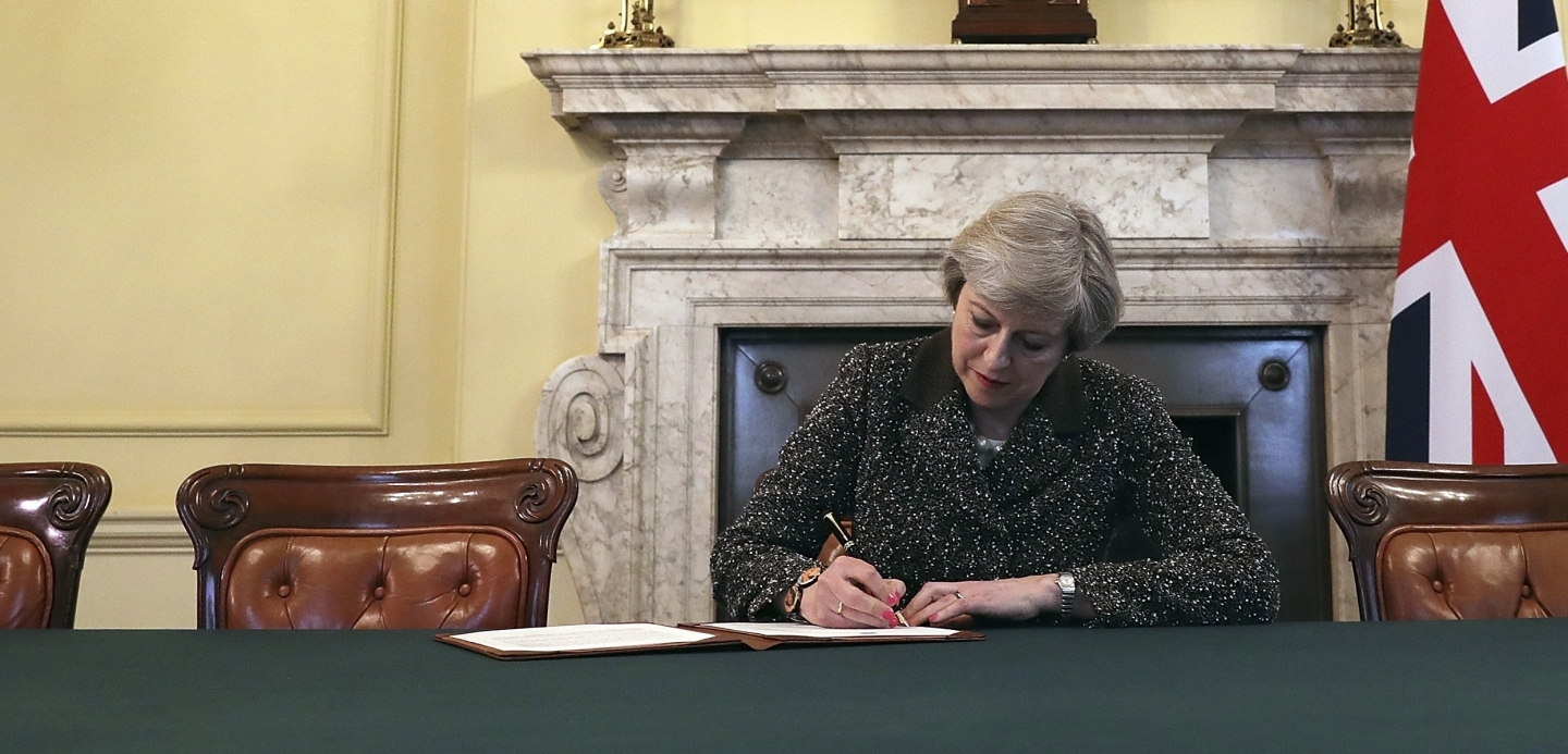 British Prime Minister Theresa May signs the official letter to European Council President Donald Tusk invoking article 50 (Christopher Furlong/Pool Photo via AP)