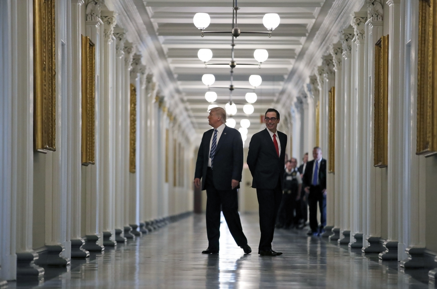 President Donald Trump walks with Treasury Secretary Steve Mnuchin as they look at portraits of the previous secretaries of the Treasury. (AP Photo/Alex Brandon)
