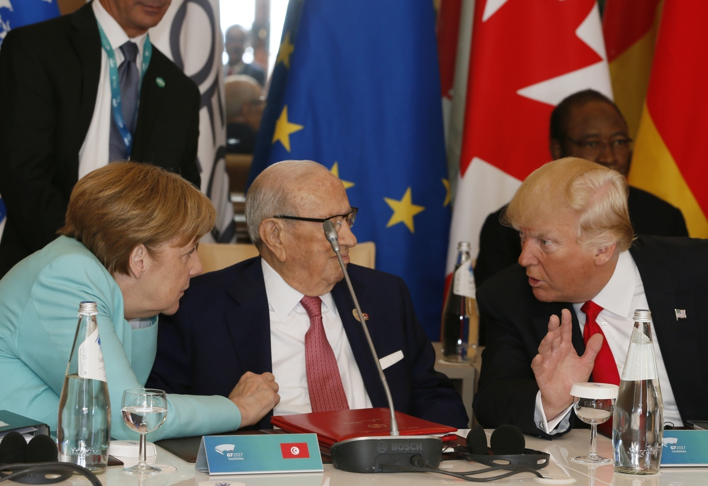 German Chancellor Angela Merkel and US President Donald Trump speak with Tunisian President Beji Caid Essebsi at roundtable during summit in Italy (AP Photo/Domenico Stinellis)