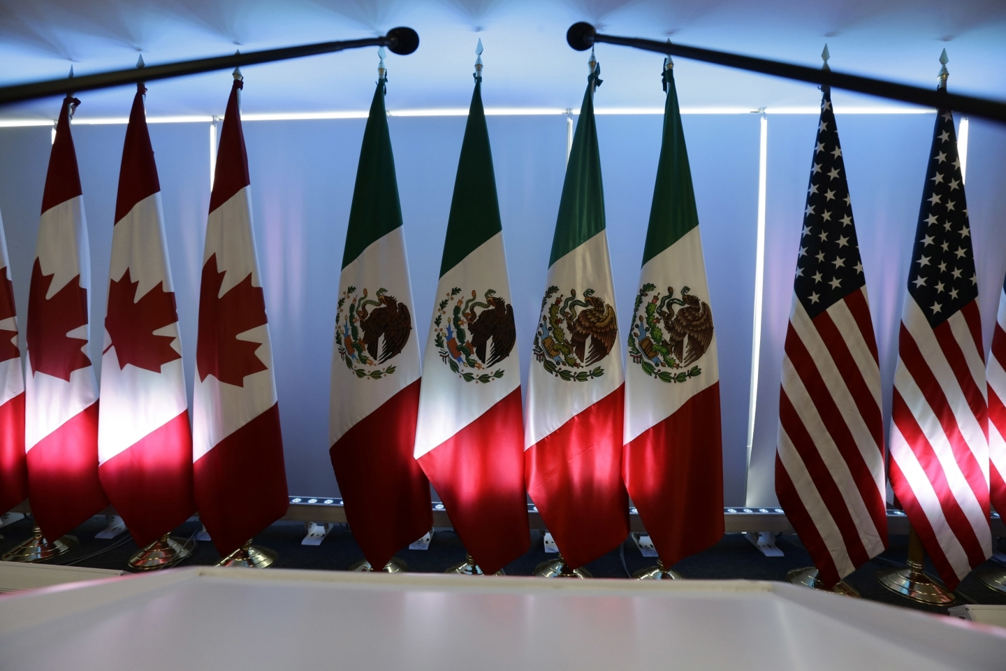 National flags representing Canada, Mexico, and the US are lit by stage lights at the NAFTA renegotiations in Mexico City, Tuesday, Sept. 5, 2017. (AP Photo/Marco Ugarte)