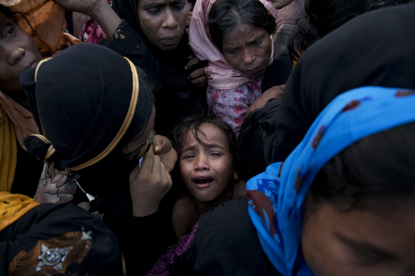 A Rohingya Muslim girl cries as she stands amid a crowd of elders in Cox's Bazar, Bangladesh (AP Photo/Bernat Armangue)