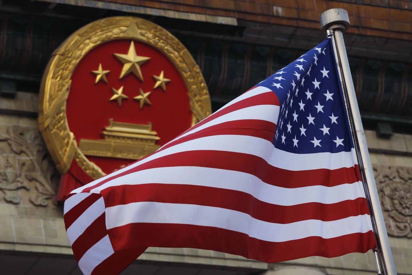 An American flag is flown next to the Chinese national emblem in Beijing (AP Photo/Andy Wong)