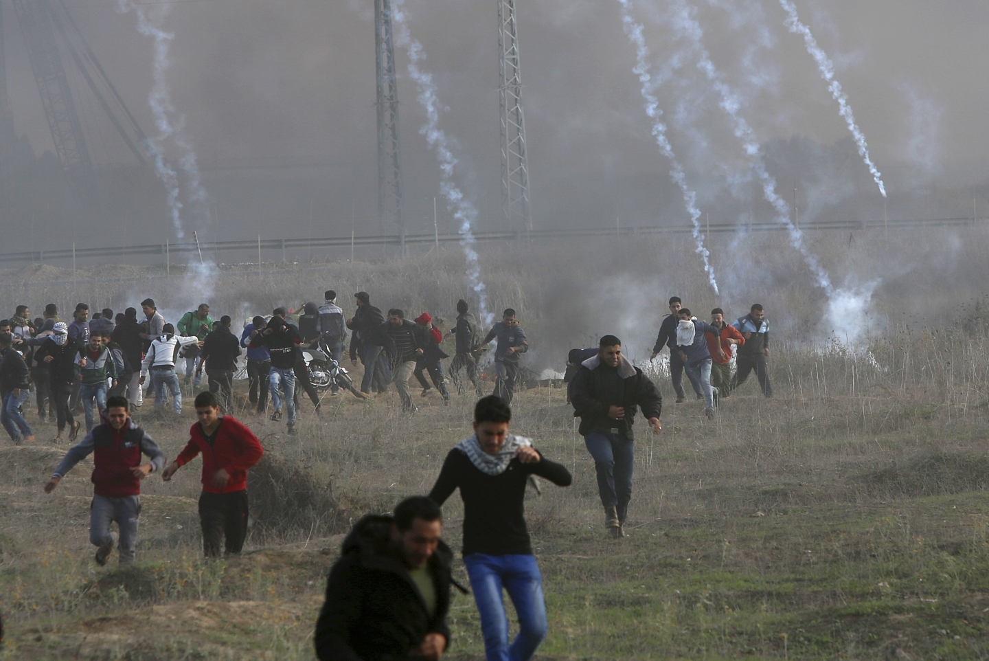 Palestinian protesters run from teargas fired by Israeli soldiers following the US decision to recognize Jerusalem as the capital of Israel. (AP Photo/Adel Hana)