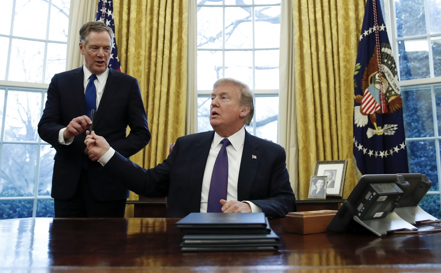 President Donald Trump, hands the pen he used to sign Section 201 actions to US Trade Representative Robert Lighthizer. (AP Photo/Carolyn Kaster)
