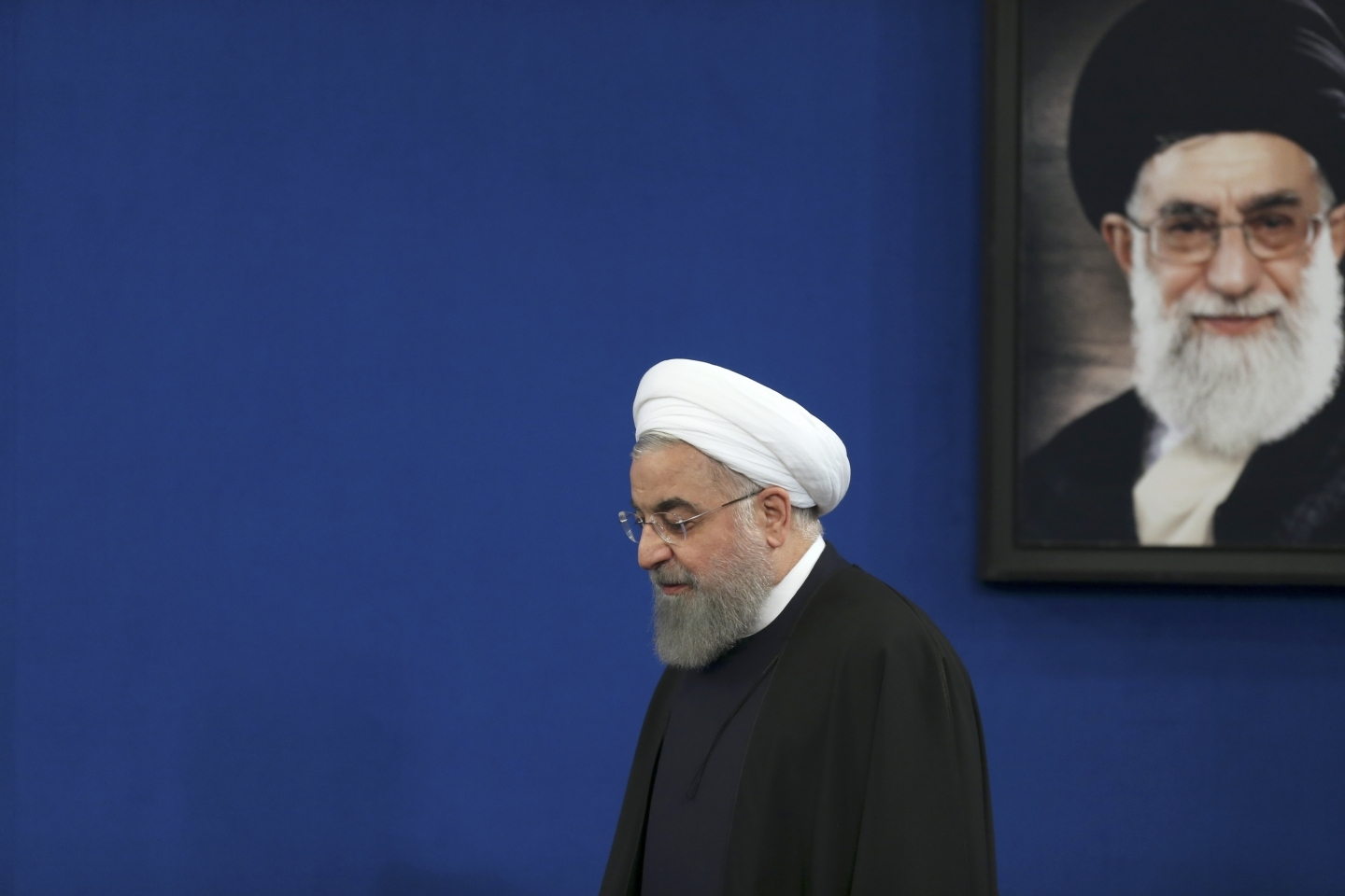 Iranian President Hassan Rouhani arrives for a press conference at the presidency compound in Tehran, Iran, Tuesday, Feb. 6, 2018. A portrait of the Supreme Leader Ayatollah Ali Khamenei hangs on the wall. (AP Photo/Vahid Salemi)