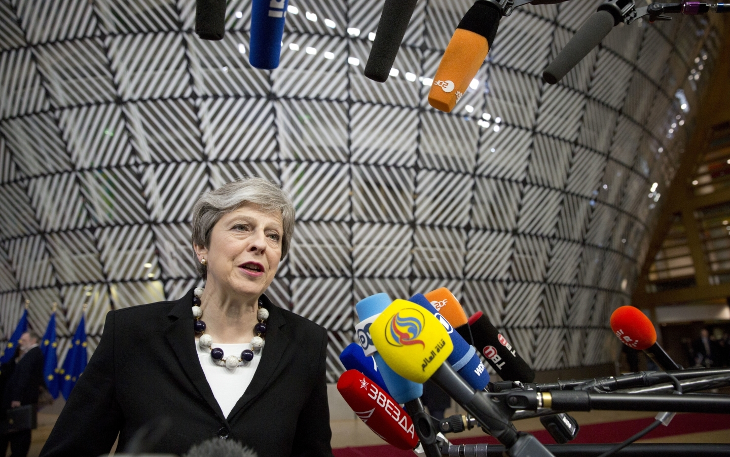British Prime Minister Theresa May speaks with the media as she arrives for an EU summit at the Europa building in Brussels on March 23, 2018. (AP Photo/Virginia Mayo)