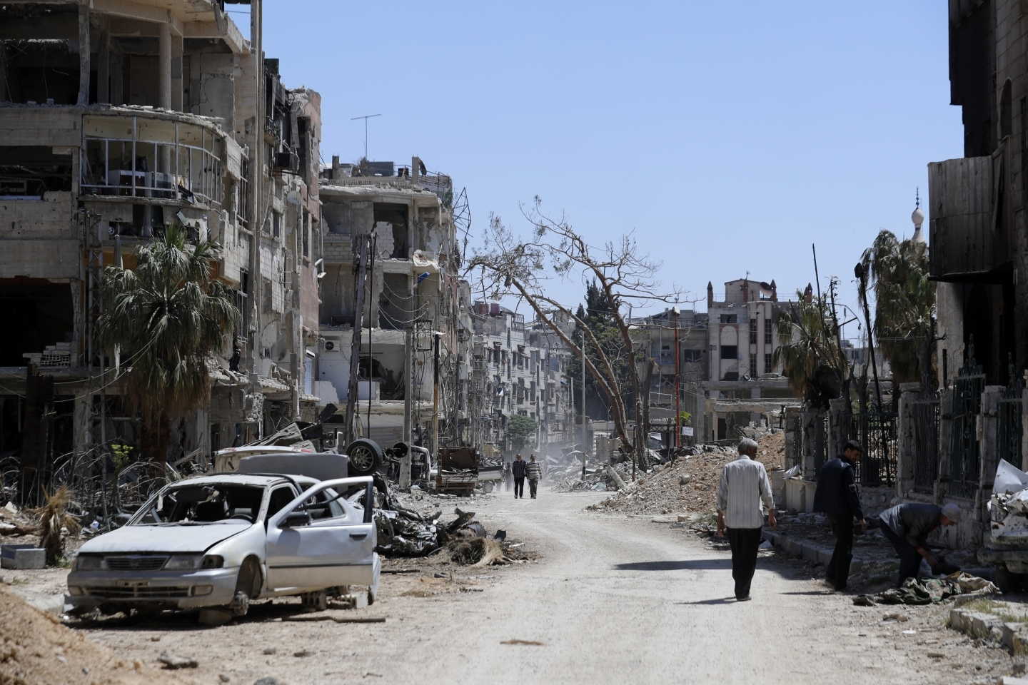 Syrians walk through destruction in the town of Douma, the site of a chemical weapons attack on Monday, April 16, 2018. (AP Photo/Hassan Ammar)
