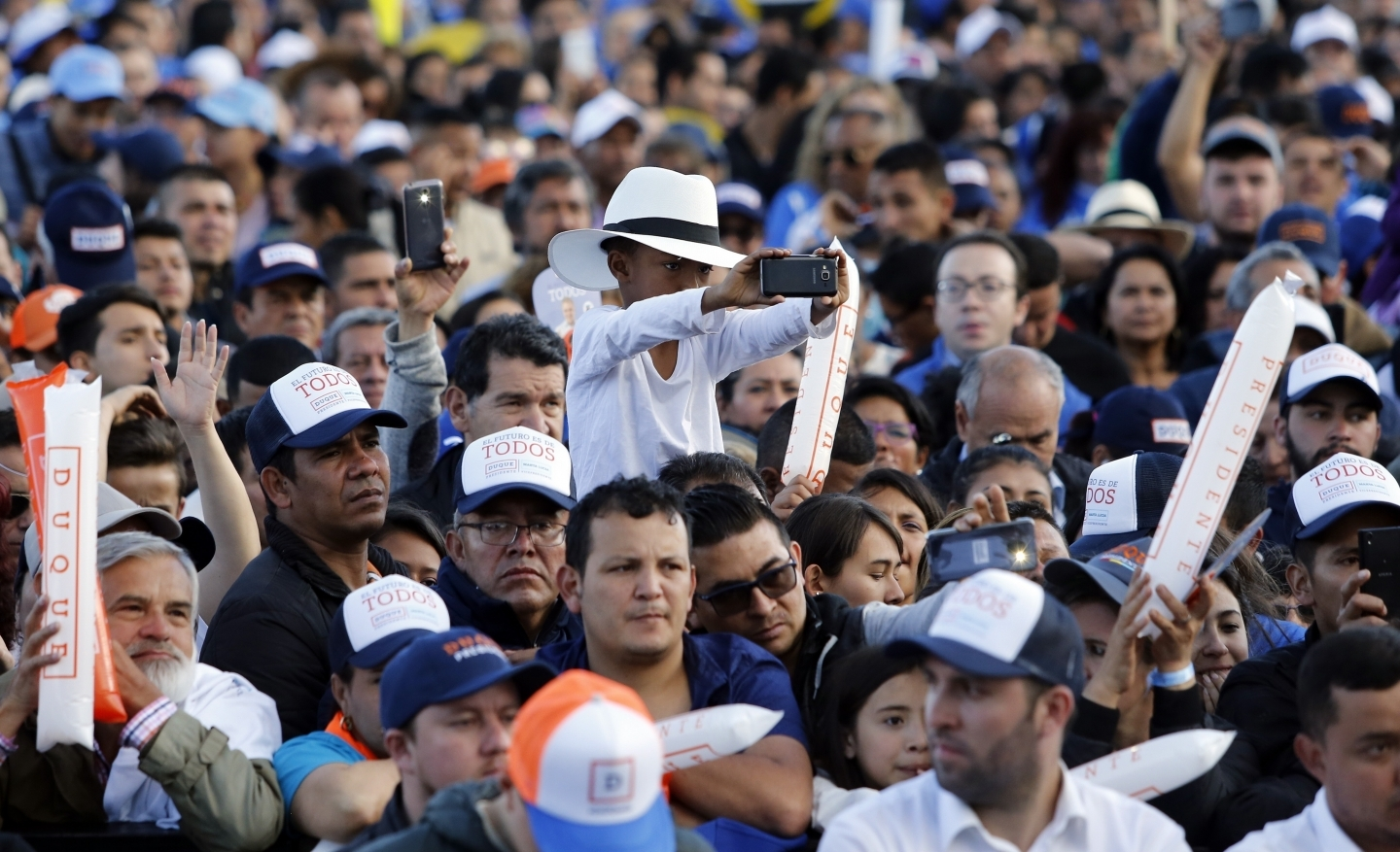 Supporters listen to Ivan Duque, presidential candidate for Democratic Center party, during his campaign rally in Bogota, Colombia on May 20, 2018. (AP Photo/Fernando Vergara)